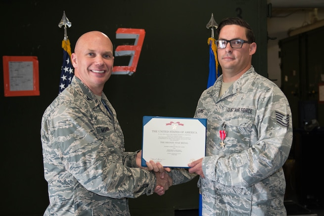 A photo of U.S. Air Force Col. Michael Manion, 55th Wing commander, presenting a Bronze Star Medal certificate to Tech. Sgt. William Adams, 55th Strategic Communications Squadron tactical radio supervisor, Aug. 7, 2018, at Offutt Air Force Base, Nebraska. This photo links to the article about the event. (U.S. Air Force photo by Zachary Hada)