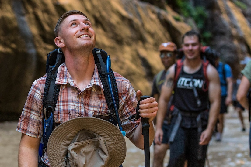 A group of people walk through a canyon.