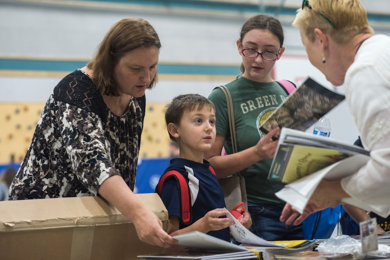 A child receives information from a Bureau of Land Management representative during the Back to School Brigade Aug. 4, 2018, at Mountain Home Air Force Base, Idaho. The Back to School Brigade event provided backpacks filled with supplies to 200 military children.