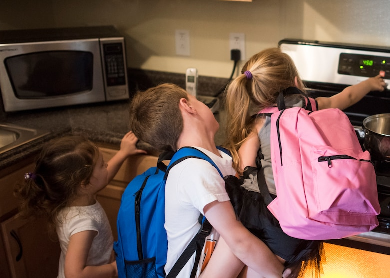 Children shut off an oven during a fire safety training Aug. 4, 2018, at Mountain Home Air Force Base, Idaho. The base firefighters brought their fire prevention trailer to teach children and families what to do during kitchen and bedroom fires.