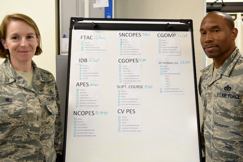 U.S. Air Force Senior Master Sgt. Brandy Hill, left, and Master Sgt. Jamell Camper, right, 20th Force Support Squadron career assistance advisors (CAA), stand next to a list of professional military education courses offered at Shaw Air Force Base, S.C., Aug. 3, 2018.