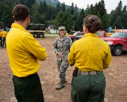 Col. Lisa McLeod, commander of the 141st Maintenance Group, laughs with Guardsmen from the 141st Air Refueling Wing while visiting the Sheep Creek fire camp in Northport, Wash. August 8, 2018. Nearly 200 Air and Army National Guardsmen were mobilized to help aid in firefighting efforts throughout Washington State. (U.S. Air National Guard photo by Staff Sgt. Rose M. Lust)