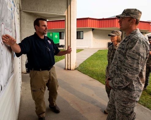 Andrew Stenbeck, the incident commander at the Sheep Creek fire camp, briefs Col. Johan Deutscher, commander of the 141st Air Refueling Wing, on the incident action plan for the Sheep Creek fire in Northport, Wash. August 8, 2018. Nearly 60 Guardsmen from the 141st ARW were mobilized to help support firefighting efforts throughout the region. (U.S. Air National Guard photo by Staff Sgt. Rose M. Lust)