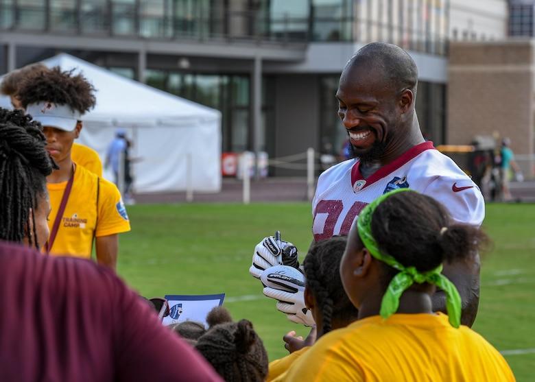 Vernon Davis, Washington Redskins tight end, autographs memorabilia during their training camp in Richmond, Virginia, August 7, 2018.