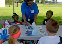 Master Sgt. Crystal Cunningham, 89th Operations Support Squadron mission operations flight chief, helps kids with a science experiment during the 7th Annual Exceptional Family Member Program Summer Camp Experience at Joint Base Andrews, Md., Aug. 7, 2018. Campers were guided through a week of STEM activities by a group of active-duty Air Force and Navy volunteers. (U.S. Air Force photo by Senior Airman Abby L. Richardson)