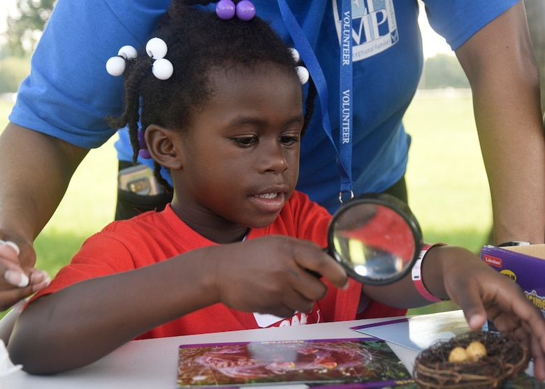 Gabrielle Scott examines objects with a magnifying glass during the 7th Annual Exceptional Family Member Program Summer Camp Experience at Joint Base Andrews, Md., Aug. 7, 2018. The camp focused on STEM-related activities and culminated in a field trip to the Smithsonian National Air and Space Museum in Washington, D.C. (U.S. Air Force photo by Senior Airman Abby L. Richardson)