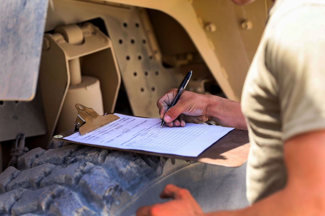 A soldier fills out a form after performing maintenance checks on a tactical vehicle.