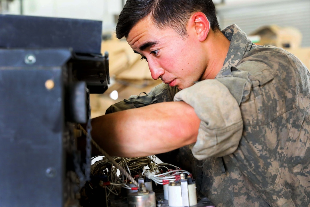 A soldier performs preventive maintenance checks and services on a generator.