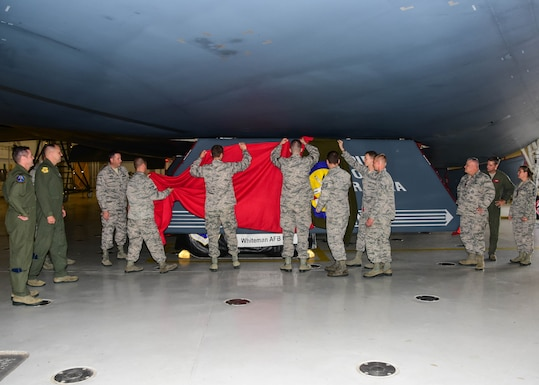 """Members of the Missouri Air National Guard's 131st Bomb Wing and the U.S. Air Force's 509th Bomb Wing unveil a new paint scheme with the slogan """"Lindbergh's Own"""" on a gear door for the Spirit of Nebraska, a B-2 bomber, at Whiteman Air Force Base, Missouri, Aug. 4, 2018. The slogan is associated with the 110th Bomb Squadron, a subordinate unit of the 131st BW, and is tied to the late Charles A. Lindbergh, the unit's most famous member. (U.S. Air National Guard photo by Senior Master Sgt. Mary Dale Amison)"""