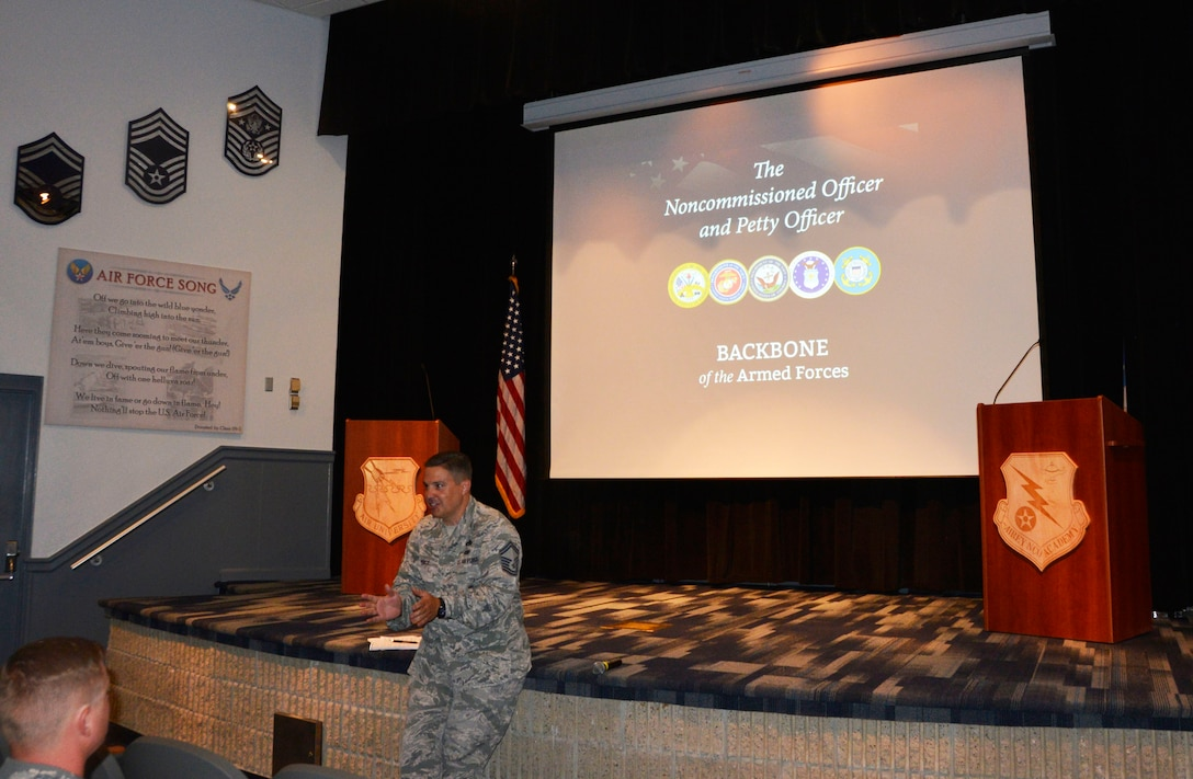 """Senior Master Sgt. Justin Price, 1st Air force Logistics Directorate, makes opening comments to students during the first day of """"Backbone University"""" July 24. Price helped lead the effort to offer the course here based on his positive experience with it at a previous assignment. Backbone University is a professional military education opportunity to gather and educate mid-level NCOs and petty officers from across NORAD and U.S. military services about joint operations and interoperability in a no-syllabus, open-ended forum. Its content is based on the senior enlisted advisor to the Chairman of the Joint Chiefs of Staff handbook, """"The Noncommissioned Officer and the Petty Officer, BACKBONE of the Armed Forces."""" Local senior enlisted facilitators each presented a chapter to the whole group, and then participants split into smaller, open-discussion groups. This class included Canadian military, U.S. Coast Guard, U.S. Air Force and U.S. Navy. (Air Force photo by Mary McHale)"""