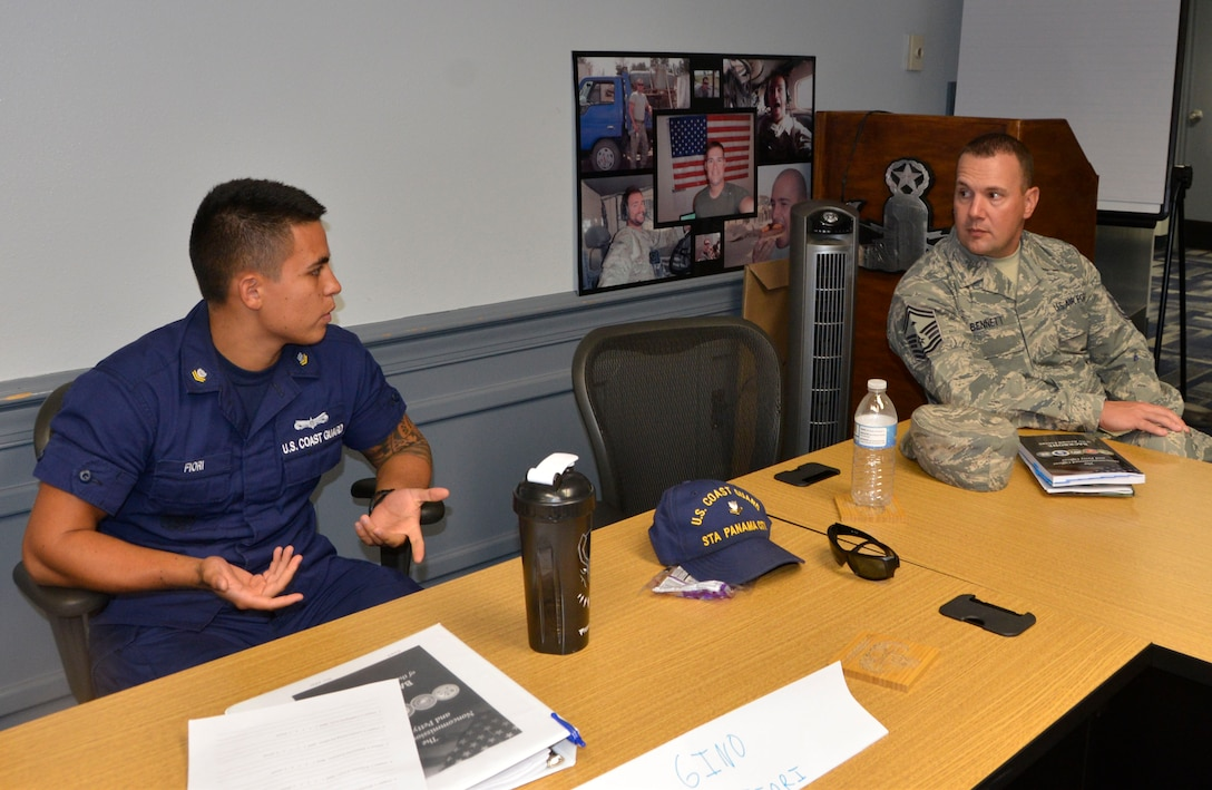"""BM2 Gino Fiori, U.S. Coast Guard Station Panama City, discusses a point with Senior Master Sgt. Jason Bennett, 1st Air Force first sergeant during the second day of Backbone University July 25. Backbone University is a professional military education opportunity that gathers and educates mid-level NCOs and petty officers from across NORAD and U.S. military services about joint operations and interoperability in a no-syllabus, open-ended forum. Its content is based on the senior enlisted advisor to the Chairman of the Joint Chiefs of Staff handbook, """"The Noncommissioned Officer and the Petty Officer, BACKBONE of the Armed Forces."""" Local senior enlisted facilitators each presented a chapter to the whole group, and then participants split into smaller, open-discussion groups. This class included Royal Canadian armed forces, U.S. Coast Guard, U.S. Air Force and U.S. Navy personnel. (Air Force photo by Mary McHale)"""