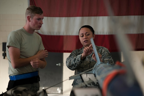 Staff Sgt. Raynette Hardcastle, right, 23d Maintenance Group lead crew chief, teaches Senior Airman Robert Monk, 23d Aircraft Maintenance Squadron weapons load crew member, during a Monthly Proficiency Required Load (MPRL), Aug. 7, 2018, at Moody Air Force Base, Ga. The weapons standardization section ensures weapons load crews are combat ready through evaluations consisting of MPRLs, semi-annual evaluations and flightline inspections. (U.S. Air Force photo by Airman Taryn Butler)