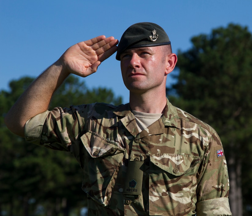 A member of the British Armed Forces honors the national anthems of each participating nation during the opening ceremony of Exercise STEPPE EAGLE 18. Exercise participation strengthens and refines peaceful military-to military relationships and underscores the U.S. committment, and increases interoperability with participating nations.