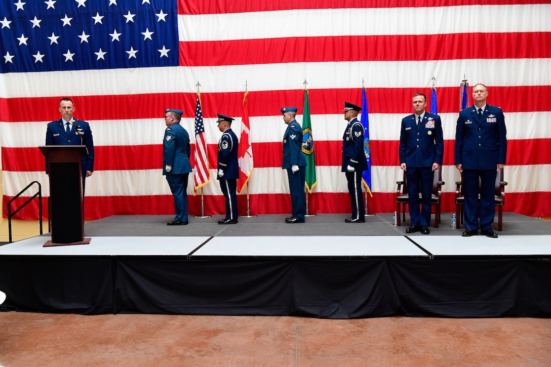 The Western Air Defense Sector Honor Guard post the colors during the WADS assumption of command ceremony at the Washington Army National Guard Readiness Center, Joint Base Lewis-McChord, Washington, July 31, 2018.  The new commander, Col. Gregory Lewis (right), stands beside the presiding officer, Brig. Gen. Kenneth Ekman, First Air Force and Air Forces Northern Command vice commander.