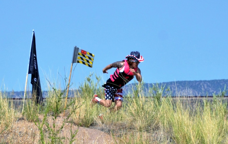 One of the participants heads back to his boat after planting his team flag on the island during the annual Cardboard Regatta at Cochiti Lake, July 27, 2018.