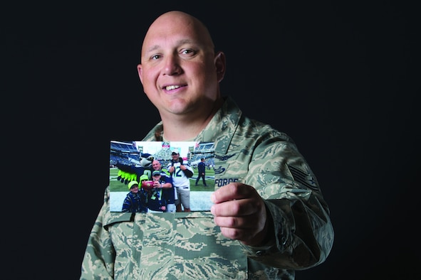 U.S. Air Force Tech. Sgt. Heath Trepanier, a 381st Intelligence Squadron analyst, holds a family photo, one of his most prized possessions, Aug. 7. Trepanier was diagnosed with leiomyosarcoma on Jan. 17, 2017. He continues to surpass the 12-month survival timeline he was given at that time.