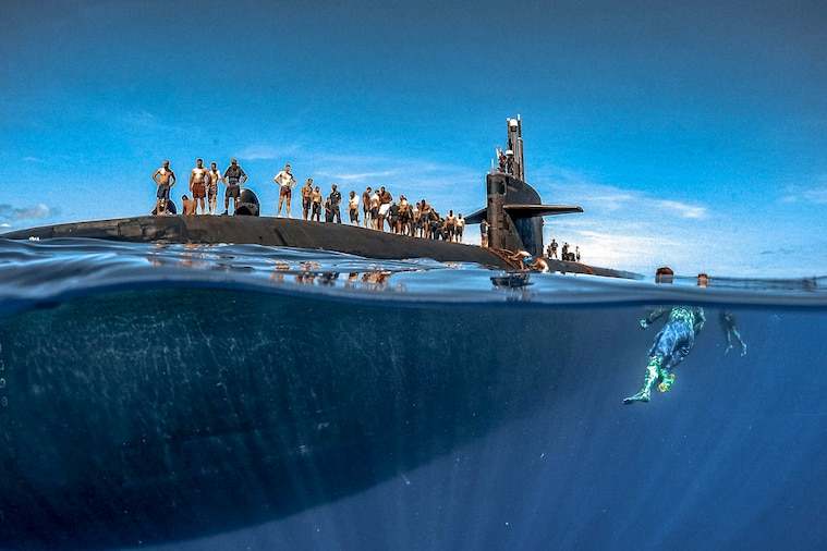 Sailors swim around a submarine.