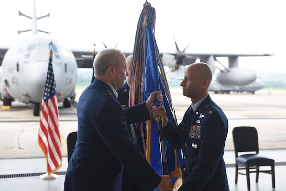 U.S. Air Force Col. Terrence Koudelka (right), receives the 193rd Special Operations Wing guidon from Brig. Gen. Mike Regan, Deputy Adjutant General - Air (left) during an assumption of command ceremony on base Aug. 11, 2018. Koudelka, as commander, is now responsible for leading one of the most deployed wings in the Air National Guard. (U.S. Air National Guard photo by Senior Airman Julia Sorber/Released).