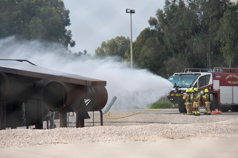 A fire truck puts out a simulated aircraft fire.