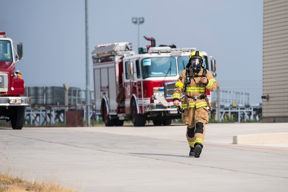 A firefighter walks to scene of simulated aircraft fire.