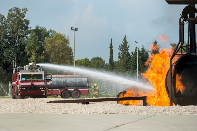 Fire truck sprays water at simulated aircraft fire.
