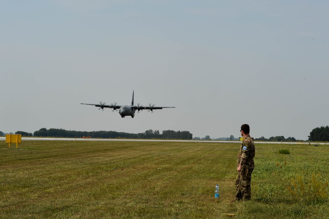 U.S. Air Force Tech. Sgt. Joshua Todd, 435th Contingency Response Group weather specialist, watches a Polish Air Force C-130E land on Powidz Air Base, Poland, Aug. 9, 2018. U.S. Airmen from Ramstein Air Base, Germany, arrived in Poland to conduct bilateral exercises with the Polish Air Force. (U.S. Air Force photo by Senior Airman Joshua Magbanua)