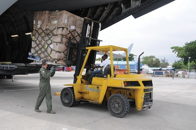 Members of the 445th Airlift Wing deliver meals to Haiti aboard a C-17 Globemaster III