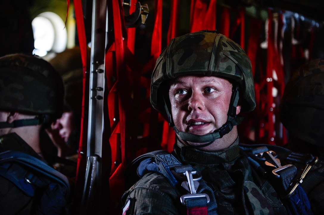 A Polish paratrooper sits down after boarding a U.S. Air Force C-130J Super Hercules at Krakow, Poland, Aug. 7, 2018. Approximately 100 Polish paratroopers jumped from two U.S. aircraft during Aviation Rotation 18-4, an annual bilateral exercise between the U.S. and Polish militaries. (U.S. Air Force photo by Senior Airman Joshua Magbanua)