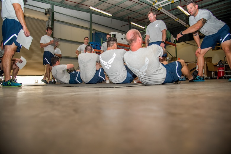 Explosive Ordnance Disposal Airmen perform the Extended Cross Knee Crunch Metronome component of the EOD Tier 2 Physical Fitness Test Prototype at Dover Air Force Base, Del., Aug. 8, 2018. The Tier 2 Physical Test prototype is designed to measure Airmen's ability to perform critical mission tasks for specific Air Force Specialty Codes.  (U.S. Air Force photo by Staff Sgt. Damien Taylor)