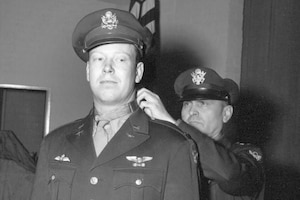 Lt. Gen. Ira Eaker places the Medal of Honor around the neck of World War II Army Air Corps 2nd Lt. John C. Morgan.