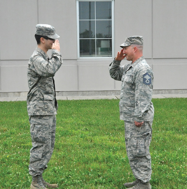 Second Lt. Jonathan Bellerive, former 445th Operations Support Squadron operation intelligence analyst, renders his first salute to Senior Master Sgt. Allen Hall, 445th OSS operation intelligence analyst, after his commissioning ceremony June 21, 2018. (U.S. Air Force photo/Stacy Vaughn)