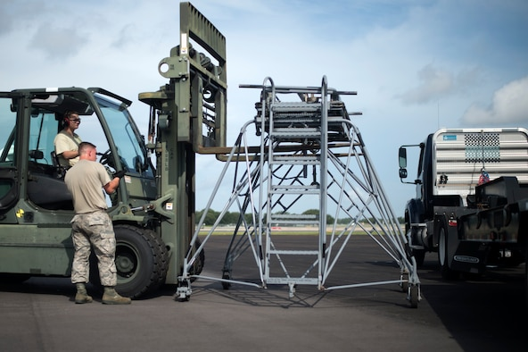 U.S. Air Force Staff Sgt. Landon Adams, training validation and operations NCO assigned to the 6th Logistics Readiness Squadron directs another Airman on how to load aircrew ground equipment (AGE) onto a trailer at Tampa International Airport (TIA) flightline, July 30, 2018.