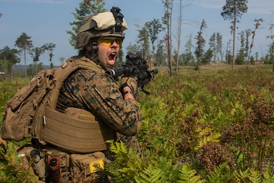 Cpl. Chandler Jones, a team leader with India Company, 3rd Battalion, 25th Marine Regiment, communicates with his Marines during a live-fire range at Camp Grayling, Mich., Aug. 8, 2018. Exercise Northern Strike is a National Guard Bureau-sponsored training exercise that unites service members from multiple branches, states and coalition countries to conduct combined ground and air combat operations. (U.S. Marine Corps photo by Cpl. Niles Lee)