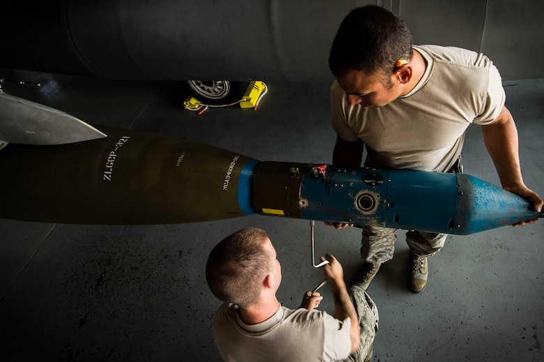 U.S. Air Force Senior Airman James Bridge, 77th Aircraft Maintenance Unit (AMU) load crew team member, left center, and Staff Sgt. Samuel Ortiz, 77th AMU load crew team lead, remove a CCG laser guided seeker from a GBU-10 at Shaw Air Force Base, S.C., Aug. 9, 2018.