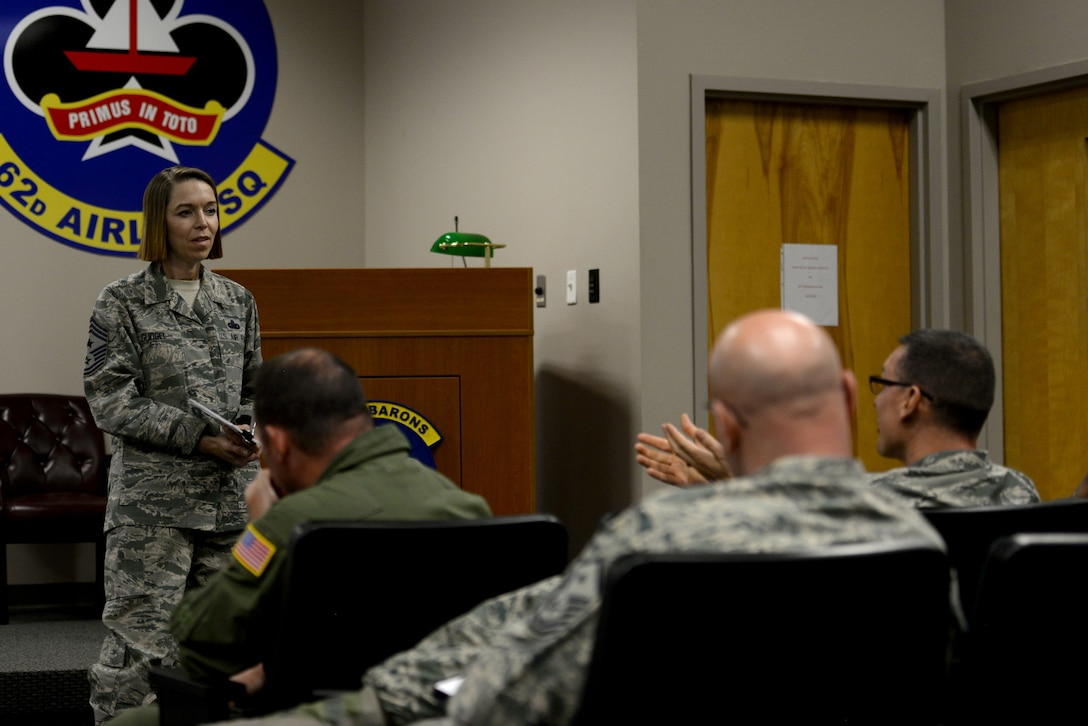 A woman in the Airman Battle Uniform looks at a man speaking to her as she stands in front of a room full seated individuals wearing ABUs.