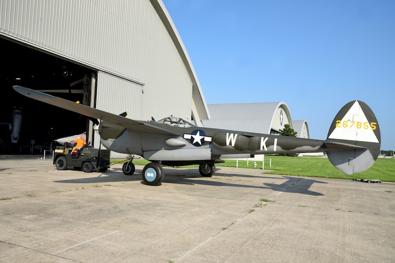 Roger Brigner, a museum restoration specialist at the National Museum of the U.S. Air Force, moves the Lockheed P-38L Lightning toward the WWII Gallery on Aug. 13, 2018. Several WWII era aircraft were temporarily placed throughout the museum to provide adequate space for the Memphis Belle exhibit opening events. (U.S. Air Force photo by Ken LaRock)