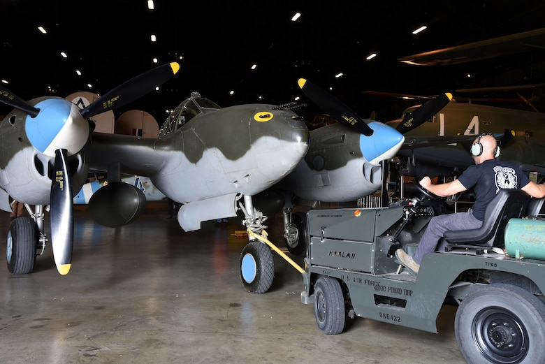 Chase Meredith, a museum restoration specialist at the National Museum of the U.S. Air Force, moves the Lockheed P-38L Lightning back into the WWII Gallery on Aug. 13, 2018. Several WWII era aircraft were temporarily placed throughout the museum to provide adequate space for the Memphis Belle exhibit opening events. (U.S. Air Force photo by Ken LaRock)