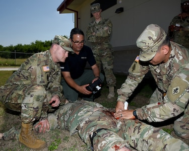 """Master Sgt. Rich Jarret (right), U.S. Army Medical Department Center and School Center for Prehospital Medicine, demonstrates how to pack a gunshot wounded with gauze on the newly fielded Tactical Combat Casualty Care-Exportable mannequin that will be used train all Soldiers on basic warrior medical skills, to Command Sgt. Maj. William """"Will"""" Rinehart, United States Army South, as Luciano Cortez, field instructor with trauma effects, controls the TC3-X and PEO-STRI clinical advisor, Lt. Col. (Dr.) Benjamin Baker looks on."""