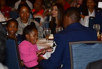 Master Sgt. Demetrius, 432nd Wing inspection superintendent, shows his award to his daughter at the Military Diversity Luncheon in Las Vegas, Aug. 9, 2018. Demetrius received the 2017 Senior Master Sgt. Margaret Frances Barbour Award for his dedication to the Remotely Piloted Aircraft enterprise, being involved in the local community and mentoring future Airmen. (U.S. Air Force photo by Airman 1st Class Haley Stevens)