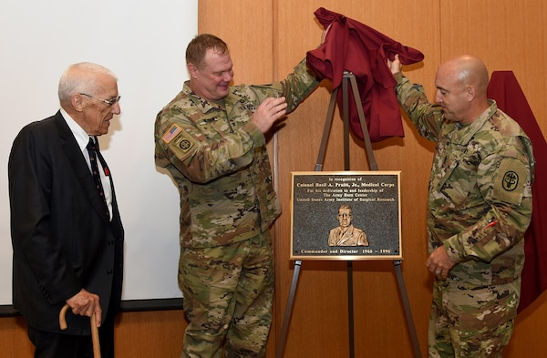 """Col. (Dr.) Shawn C. Nessen (center), U.S. Army Institute of Surgical Research commander, and the USAISR Senior Enlisted Advisor, Sgt. Maj. William """"Dave"""" Poist Jr., unveil a bronze plaque for Dr. Basil Pruitt Jr., during the USAISR 70thAnniversary Symposium July 18 at Joint Base San Antonio-Fort Sam Houston."""