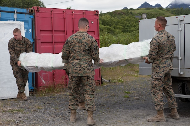 Marines with Marine Wing Support Squadron 471, 4th Marine Aircraft Wing unload a shipment of construction equipment during Innovative Readiness Training, Old Harbor, Alaska, Aug. 5, 2018. This year marks the completion of the 2,000-foot extension of Old Harbor's runway. (U.S. Marine Corps photo by Lance Cpl. Tessa D. Watts)