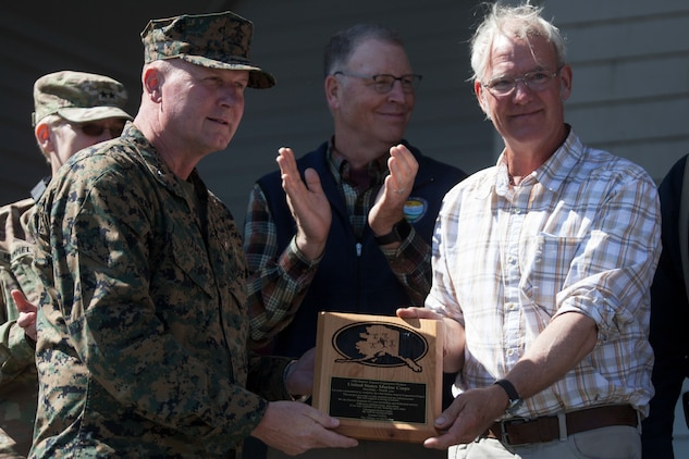 The Mayor of Old Harbor, Rick Berns presents a plaque to Brig. Gen. Bradley S. James, commanding general of 4th Marine Aircraft Wing, at the Old Harbor School Aug. 7, 2018. The plaque was awarded to Marine Forces Reserve to thank them for their commitment and dedication while constructing the extended runway as a part of Innovative Readiness Training Old Harbor, Alaska. (U.S. Marine Corps photo by Lance Cpl. Tessa D. Watts)