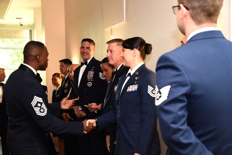 U.S. Air Force Chief Master Sgt. Lavor Kirkpatrick, 17th Training Wing command chief, congratulates senior noncommissioned officer inductees before the medallion ceremony at the Event Center on Goodfellow Air Force Base, Aug. 10, 2018. Goodfellow members came together to congratulate the inductees on their accomplishments and hard work up to this moment of joining the ranks of senior NCOs stepping from the role of first line supervisors to leaders of operational competence. (U.S. Air Force photo by Airman 1st Class Seraiah Hines/Released)