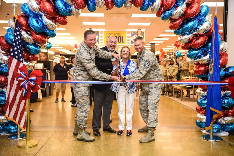 319th Air Base Wing Commander Col. Benjamin Spencer cuts the ribbon on the renovated Army & Air Force Exchange Service exchange during a grand reopening celebration August 10th alongside AAFES Central Regional Vice President Larry Salgado, Exchange General Manager Annette Montgomery, and 319th Air Base Wing Command Chief Master Sergeant Brian Thomas. Since 1895 AAFES has supported America's military men and women and completed store renovations within six months at Grand Forks Air Force Base, North Dakota.