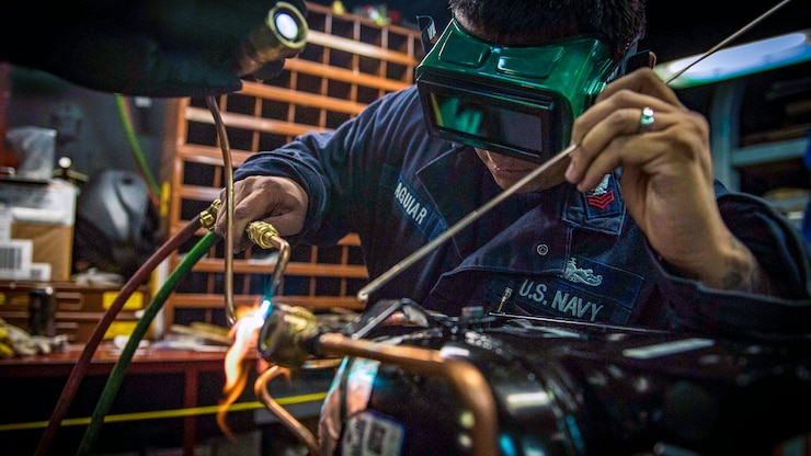 A sailor uses a welding torch aboard the USS Carney.
