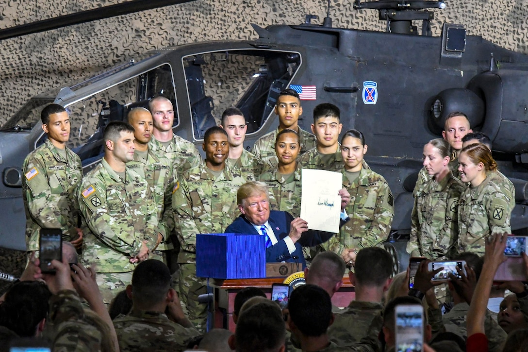 President Donald J.Trump poses with service members in front of a helicopter.