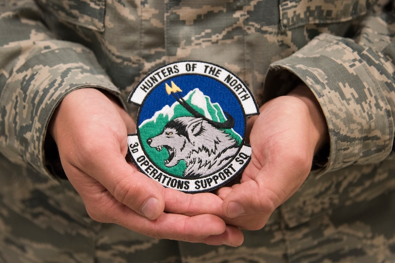U.S. Air Force Staff Sgt. Paul Babbitt, with the 3rd Operations Support Squadron aerospace flight equipment section, holds the 3rd OSS patch he designed at Joint Base Elmendorf-Richardson, Alaska, July 12, 2018. Babbitt had the opportunity to design the new patch after squadron leadership thought an update was necessary.