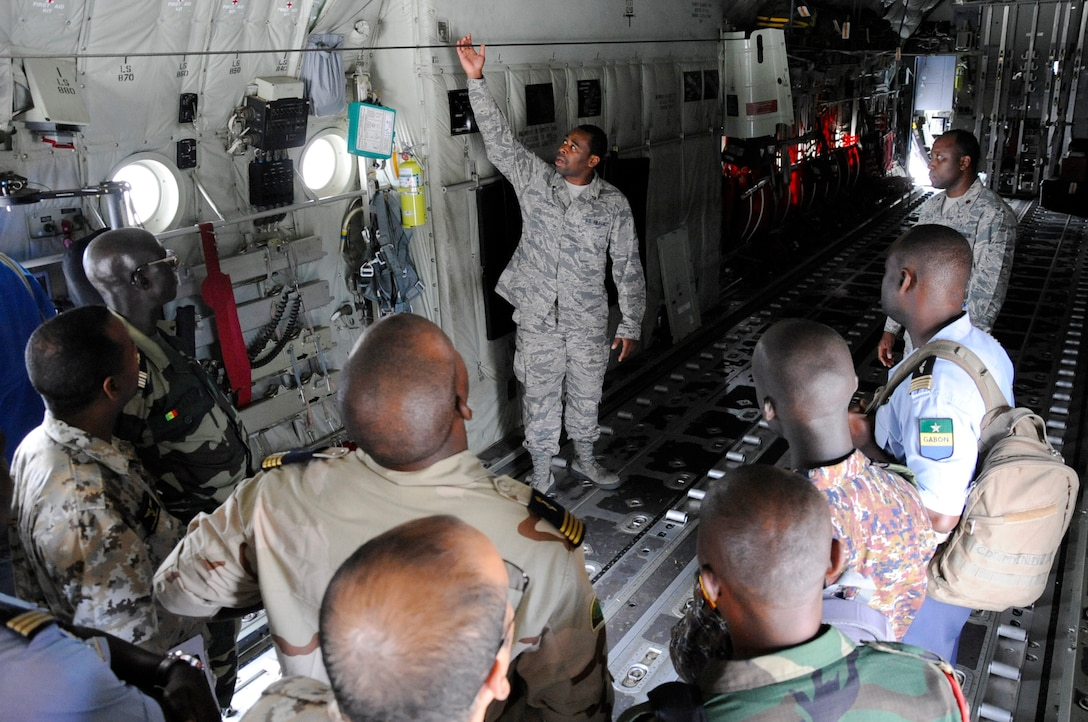 U.S. Air Force Staff Sgt. Kyle Chestnut, a Flying Crew Chief assigned to 86th Air Maintenance Squadron, shows the inside of a C-130 aircraft to participants of African Partnership Flight, hosted by U.S. Air Forces Africa and co-hosted by Mauritania and Senegal at Ramstein Air Base, Germany, Aug. 7, 2018. The APF program is Air Forces in Africa's premier security cooperation program with African partner nations to improve professional military aviation knowledge and skills. (U.S. Army photo by Spc. Craig Jensen)