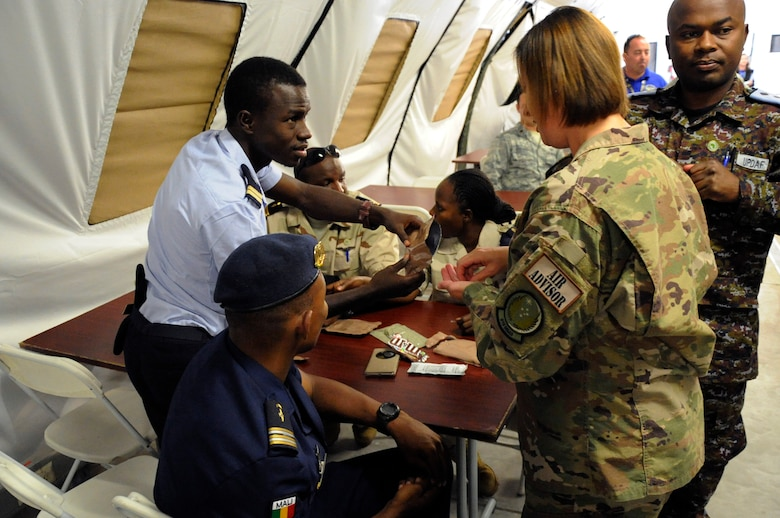 Lt. Yassive Mahamat Brahim, a helicopter technician in the Chad air force, shares a Meal Ready to Eat with U.S Air Force Master Sgt. Emily Vaughn, a Personalist assigned to 818th Mobility Support Advisory Squadron during the African Partnership Flightat Ramstein Air Base, Germany, Aug. 9, 2018. The APF program is Air Forces in Africa's premier security cooperation program with African partner nations to improve professional military aviation knowledge and skills. (U.S. Army photo by Spc. Craig Jensen)