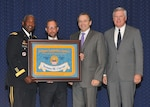 DLA Director Army Lt. Gen. Darrell Williams (far left) and former DLA directors Vice Adm. Mark Harnitchek (second from right) and Vice Adm. Alan Thompson (far right), present DLA General Counsel James Coyne an honorary DLA flag during his retirement ceremony Aug. 10 at the McNamara Headquarters Complex, Fort Belvoir, Virginia. Photo by Teodora Mocanu.